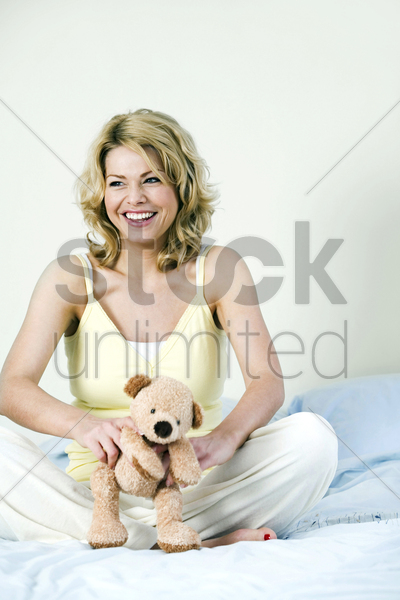 a woman playing with a teddy bear stock photo