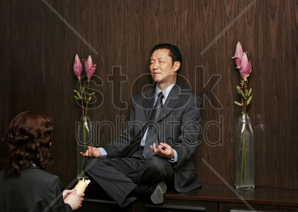 a woman praying in front of a man who is sitting on a shelf meditating stock photo