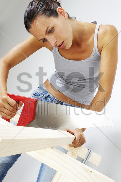 a woman sawing a wood stock photo