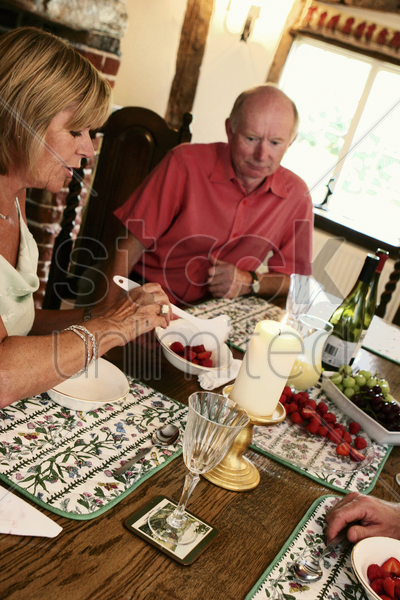 a woman scooping some cut strawberries while her husband watching stock photo