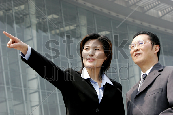 a woman showing something to a bespectacled man stock photo