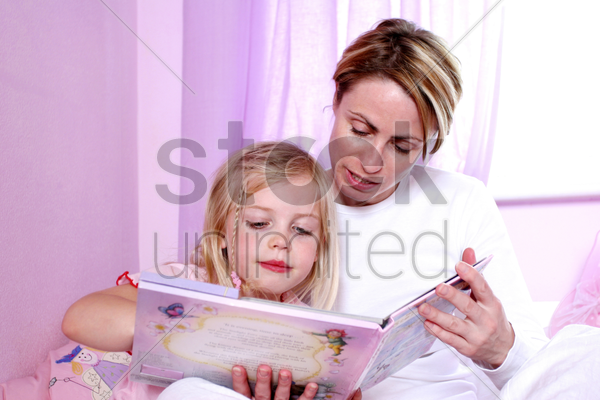 a woman sitting on the bed reading bedtime story for her daughter stock photo