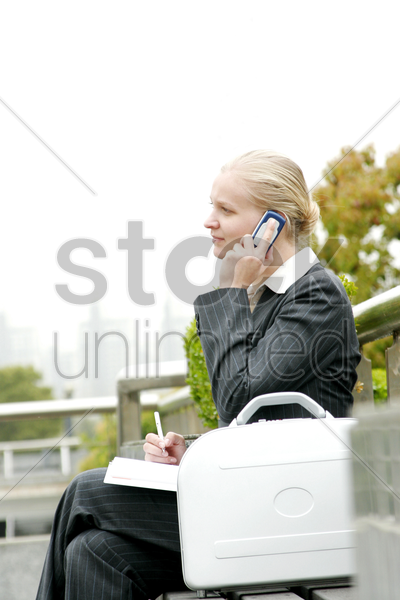 a woman sitting on the bench talking on the hand phone stock photo