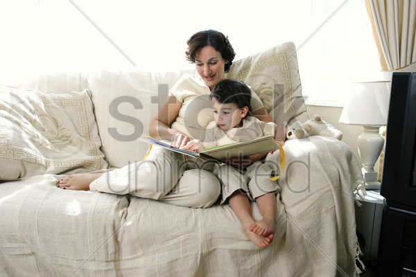 a woman sitting on the couch reading a story book for her young son stock photo