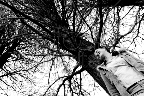 a woman standing under a tree stock photo
