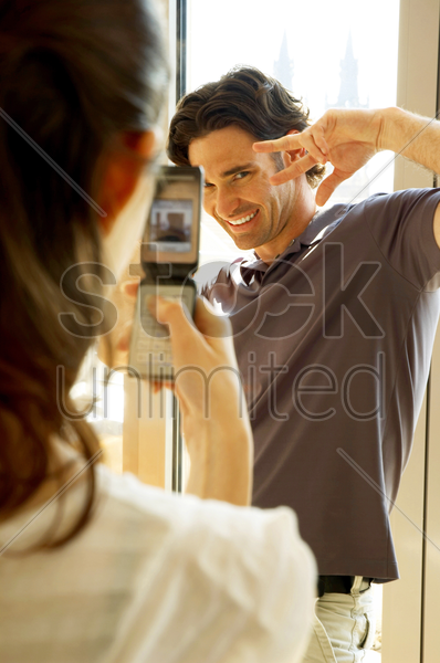 a woman taking her husband's picture with her camera phone stock photo
