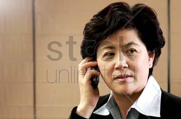 a woman talking on the hand phone stock photo