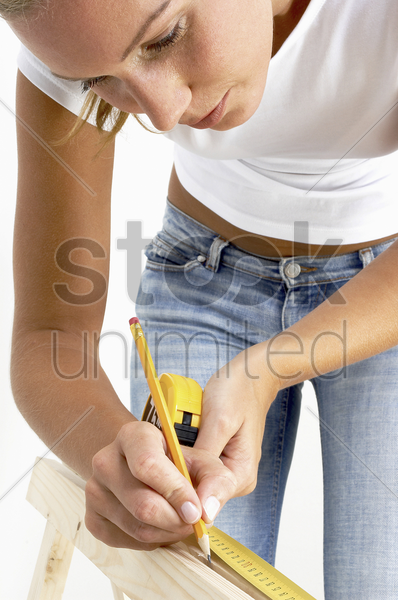 a woman using a pencil to mark the measurement on the wood stock photo