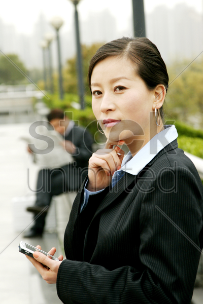 a woman using palmtop and a man reading newspaper stock photo