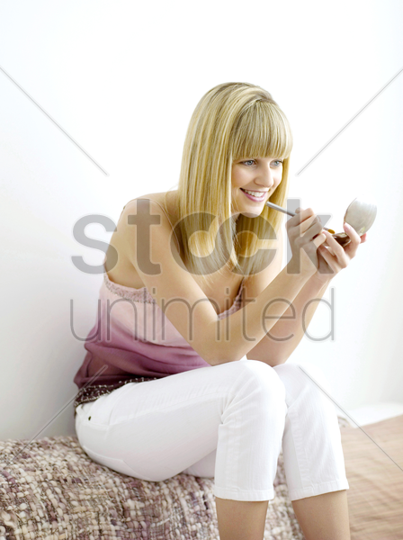 a woman using press powder stock photo