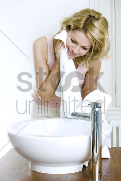 a woman washing her face stock photo
