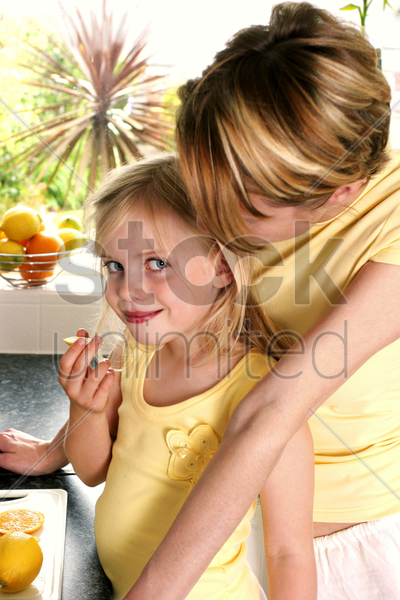 a woman watching her daughter eating lemon stock photo