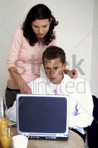 a woman watching her husband playing with his laptop on the dining table stock photo