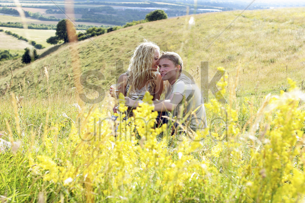 a woman whispering a little something to her boyfriend on the prairie stock photo