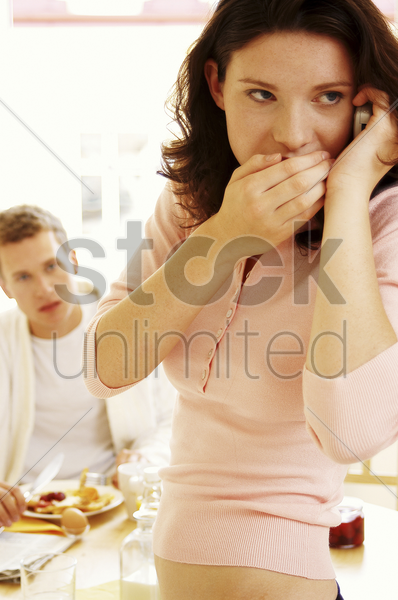 a woman whispering on the hand phone as her husband watching suspiciously stock photo