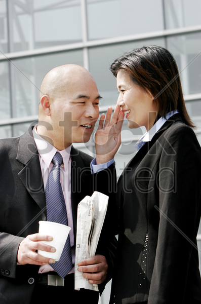 a woman whispering something to a bald man stock photo