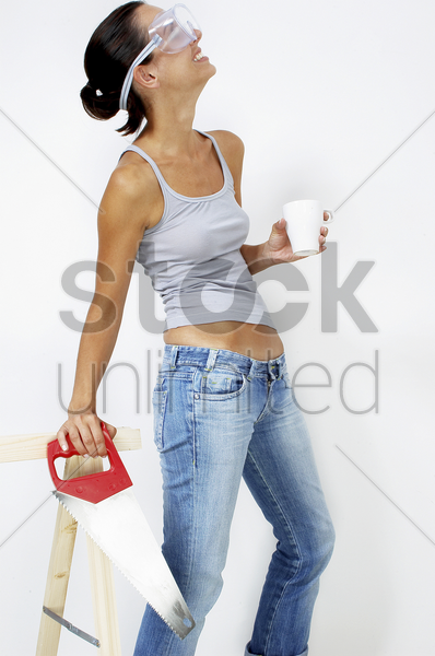 a woman with goggles holding a cup and a saw stock photo