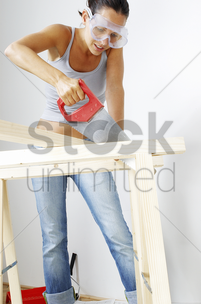 a woman with goggles sawing a wood stock photo