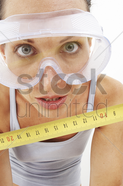 a woman with goggles using a measuring tape to measure the camera stock photo