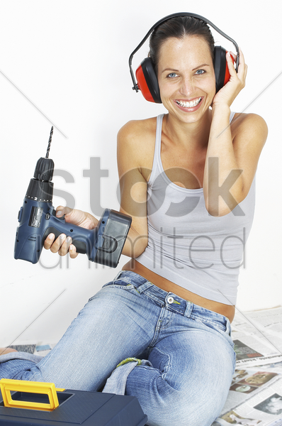 a woman with headphone sitting on the floor holding a driller stock photo