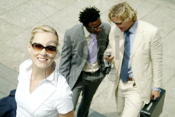 a woman with sunglass walking up the stairs with two men walking behind stock photo