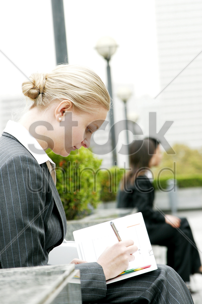 a woman writing something on her organizer stock photo