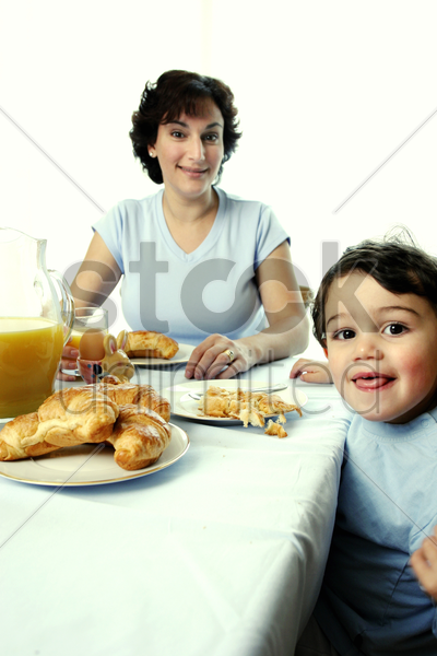a young boy having breakfast together with his mother stock photo