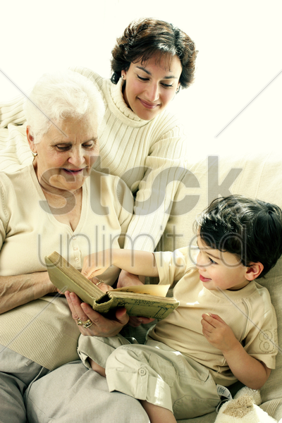 a young boy having fun learning from his grandmother and mother stock photo
