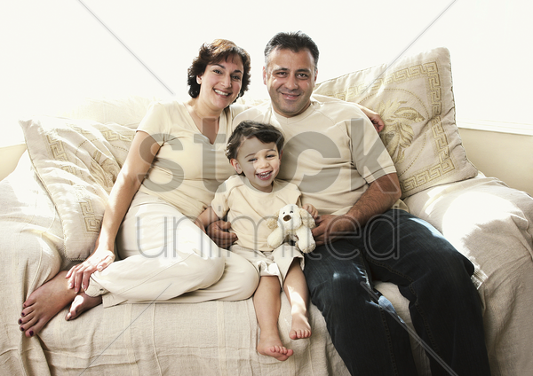 a young boy sitting between his father and mother on the couch stock photo