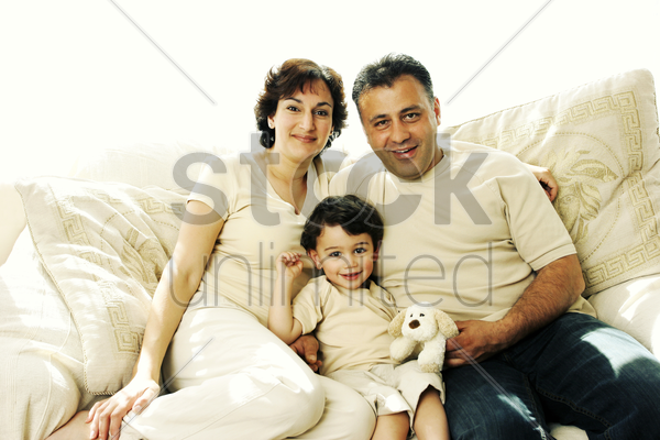 a young boy sitting on the couch with his parents stock photo