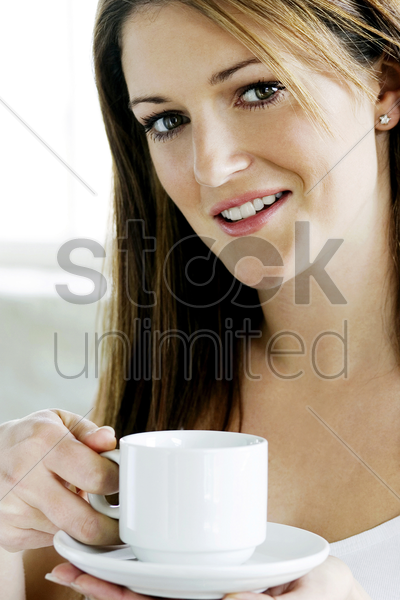 a young lady looking at camera while holding a cup of coffee stock photo