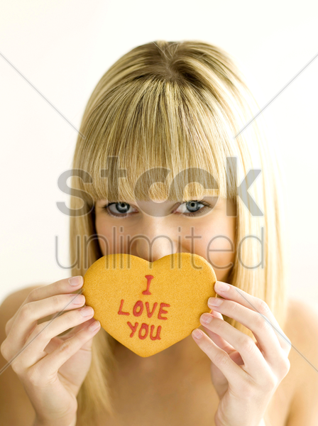 a young teen holding a cookie with both hands stock photo