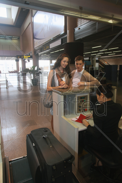 airline check-in attendant checking passports of man and woman at the airport check-in counter stock photo