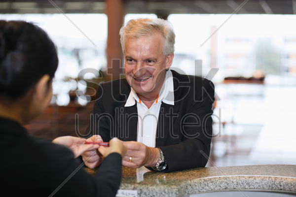 airline check-in attendant returning businessman's passport at the airport check-in counter stock photo