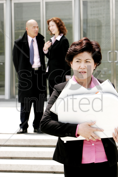 an angry looking woman holding a briefcase of papers stock photo