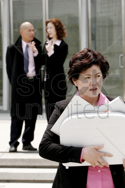 an angry woman carrying a briefcase of documents stock photo