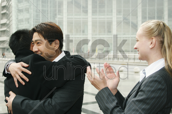 an asian man hugging his friend while a lady clapping her hands stock photo