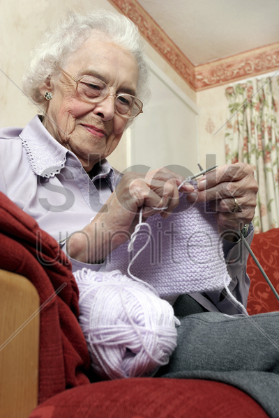 an old bespectacled woman sitting on the couch knitting stock photo