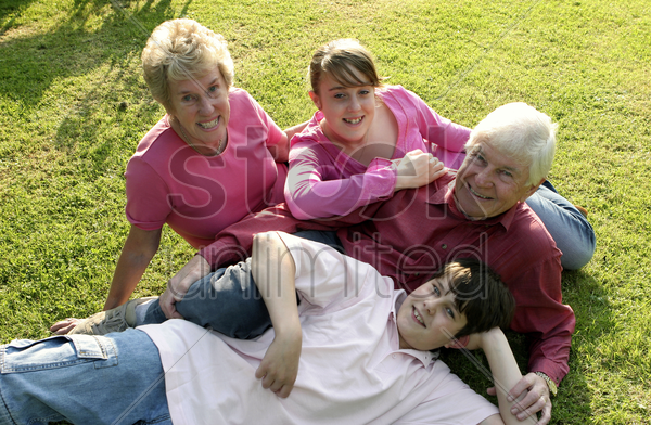 an old couple lying on the field with their grandchildren for a group photo stock photo