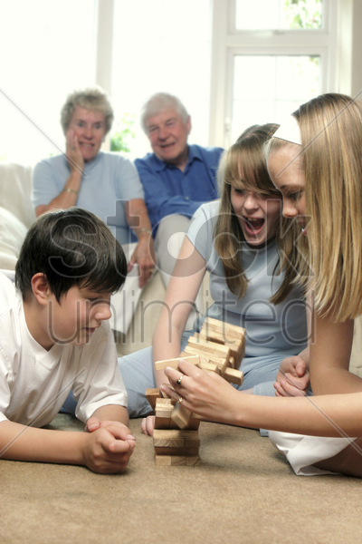 an old couple sitting on the couch watching their grandchildren playing building blocks on the floor stock photo