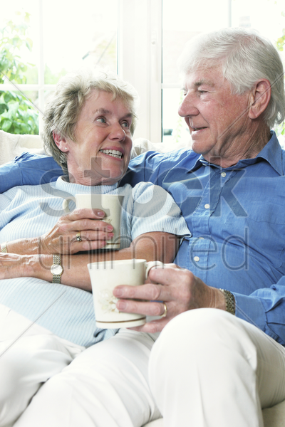 an old couple sitting together on the couch holding cups stock photo