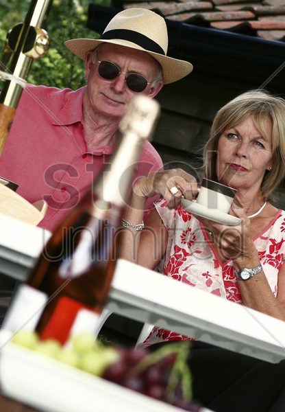 an old man with straw hat and sunglasses sitting in the backyard with his wife stock photo