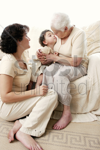 an old woman hugging her grandson while her daughter watching stock photo