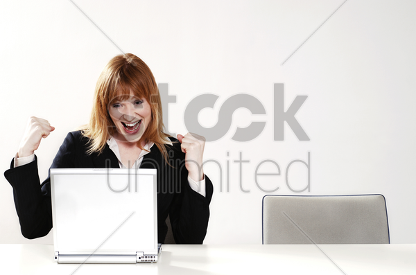 an overjoyed businesswoman after reading the good news on her laptop stock photo