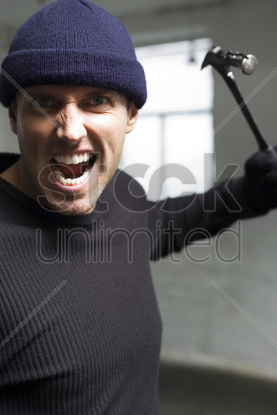 angry burglar attacking with a hammer stock photo