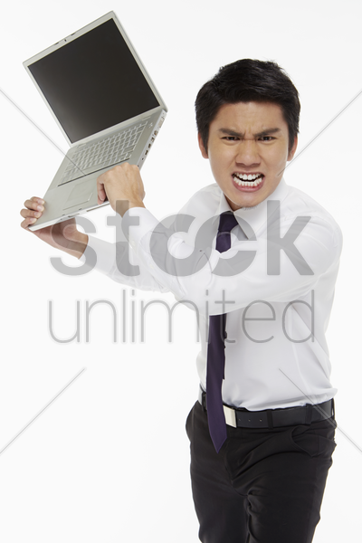 angry businessman throwing a laptop stock photo