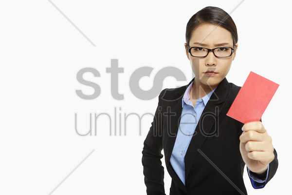 angry businesswoman holding up  a red card stock photo