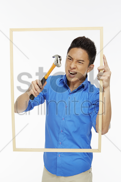 angry man hitting a picture frame with hammer stock photo