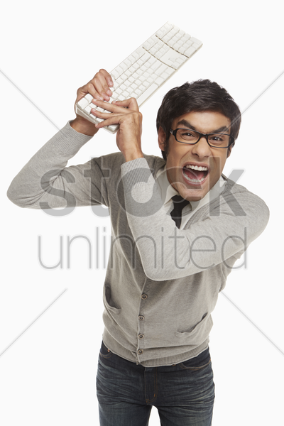 angry man holding up a computer keyboard stock photo