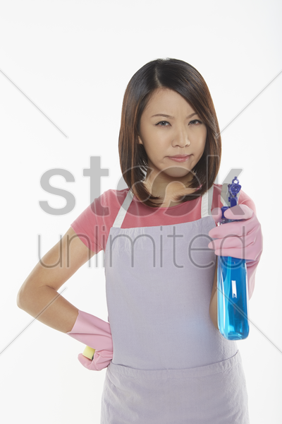 angry woman holding out a spray bottle stock photo